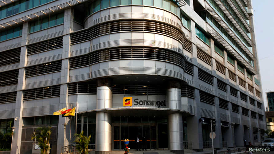 A woman walks past the head office of Angola's state oil company Sonangol in the capital Luanda, Angola, Aug. 26, 2012.