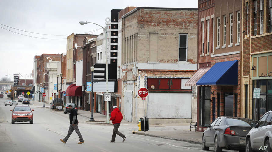 Local residents walk across Main Street, Friday, Jan. 27, 2017, in Ottumwa, Iowa.Far from the cacophony enveloping Washington in President Donald Trump's first week in office, the Iowa voters who helped him capture the state and the presidency last