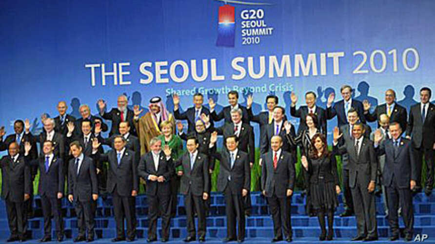 Members of the G20 wave during the family photo session at the G20 Summit in Seoul. Leaders of the world's 20 biggest economies faced the urgent task at their summit Friday of resolving a U.S.-China currency dispute that has raised the specter of a g