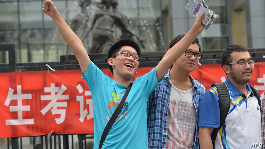 """A student pose for a photo after taking the 2014 college entrance exam of China, or the """"gaokao"""", outside a high school in Beijing, June 8, 2014.."""