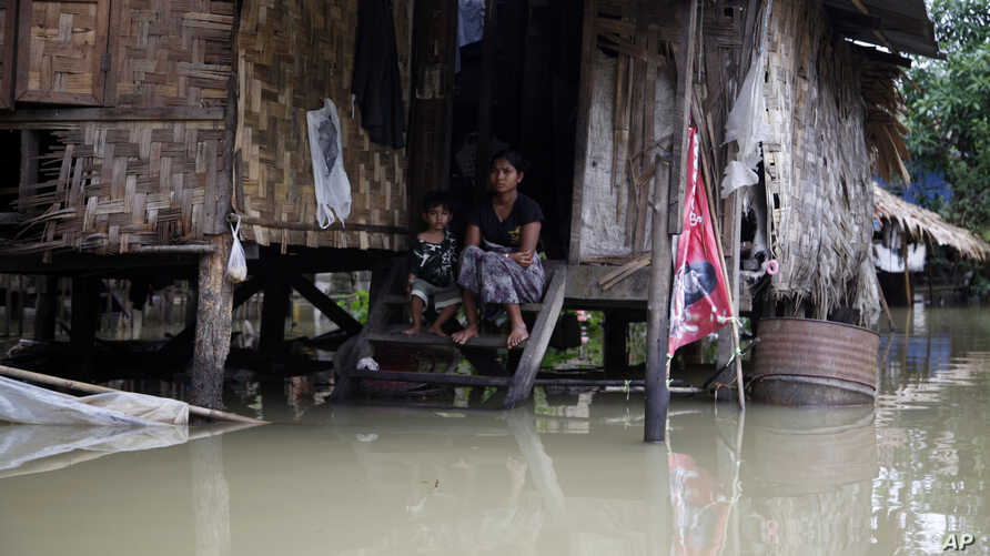 A woman and her child look out from their residence half-submerged in floodwaters in Bago, 80 kilometers northeast of Yangon, Myanmar, Saturday, Aug 1, 2015.