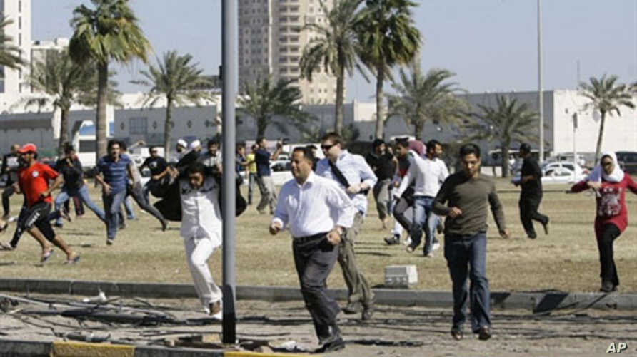 Bahraini anti-government protesters run for cover in Manama on February 19, 2011 after police fired tear gas to disperse them at Pearl Square