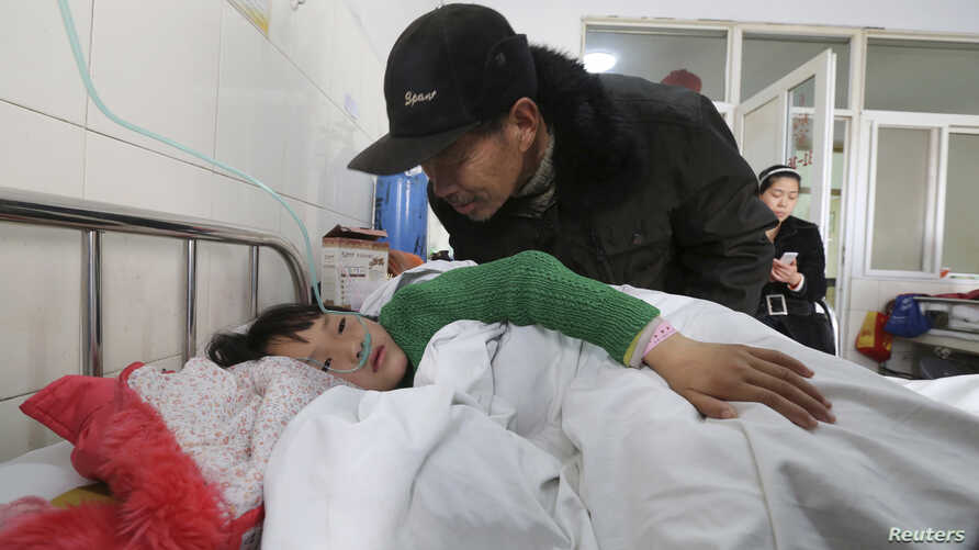 An elderly man talks to a girl who was injured after a stampede accident at a primary school, at a hospital in Xiangyang, Hubei province, China, Feb. 27, 2013.