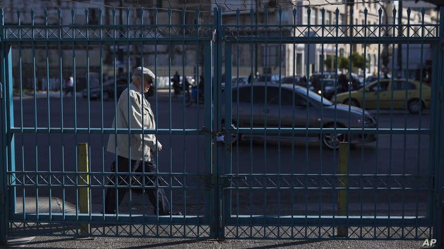 Greece BailoutA man walks behind a locked passengers entrance of Athens' port of Piraeus which is on strike, on May 6, 2016.
