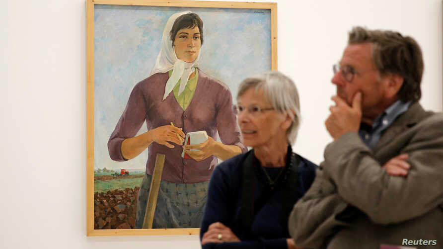 "Visitors stand in front of the painting ""The Brigadier"" by Albanian artist Spiro Kristo during the Documenta 14 art exhibition in the National Museum of Contemporary Art in Athens, Greece, May 9, 2017."