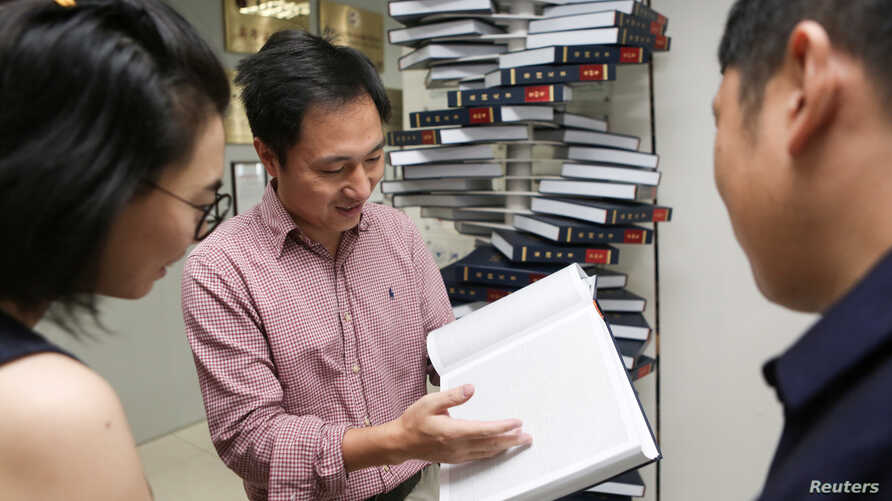 "FILE - Scientist He Jiankui shows ""The Human Genome"", a book he edited, at his company Direct Genomics in Shenzhen, Guangdong province, China, Aug. 4, 2016."