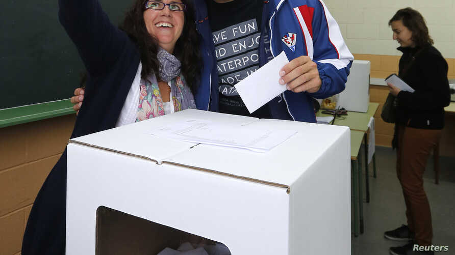 """FILE - A couple take a selfie while casting their ballots in Mataro, near Barcelona, Nov. 9, 2014. In the United States, various states are weighing whether to allow """"I Voted"""" selfies in the ballot booth."""
