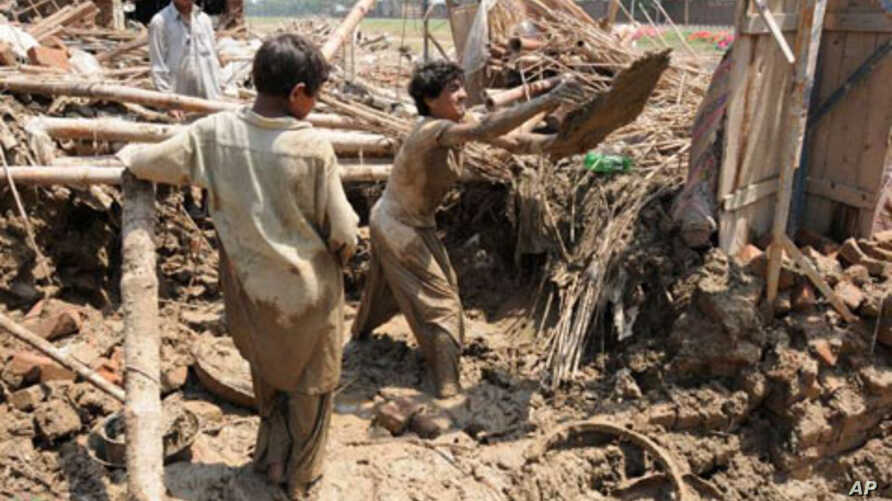 Men digging up the remains of their home in the Azakhel refugee camp, near Peshawar, following the floods that have left much of Pakistan in misery, Aug 2010