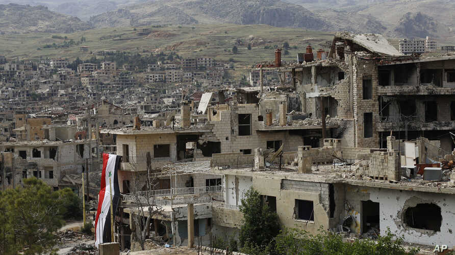 FILE - A Syrian national flag hangs from a damaged building in the town of Zabadani in southwestern Syria, May 18, 2017.
