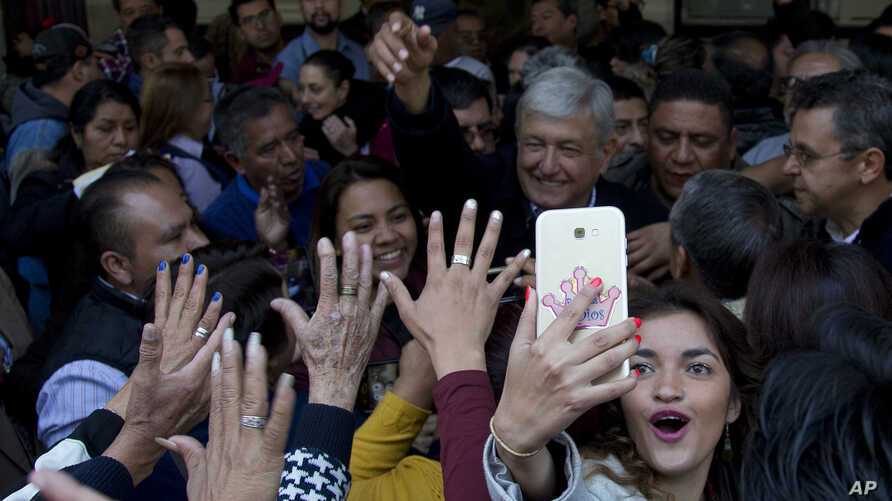 A woman takes a selfie backdropped with presidential hopeful Andres Manuel Lopez Obrador during a pre-campaign rally in Mexico City, Friday, Dec. 15, 2017. ON Feb. 7, 2018, reports say Lopez Obrador has an 11-point lead over rivals, according to an o