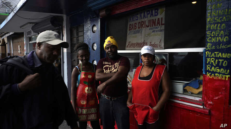 Haitian immigrant Wilthene Pierre is pictured with two of his cooks Emily, left, and Violette Novembre, in front of the Kriskapab Baborijinal Haitian restaurant in Tijuana, Mexico, Nov. 22, 2018. The bright blue-and-red cafe serves Mexicans and Haiti