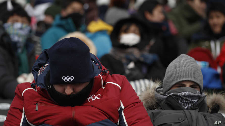Spectators, with their faces covered, waiting for the start of the women's slopestyle qualifications at Phoenix Snow Park at the 2018 Winter Olympics in Pyeongchang, South Korea, Feb. 11, 2018.