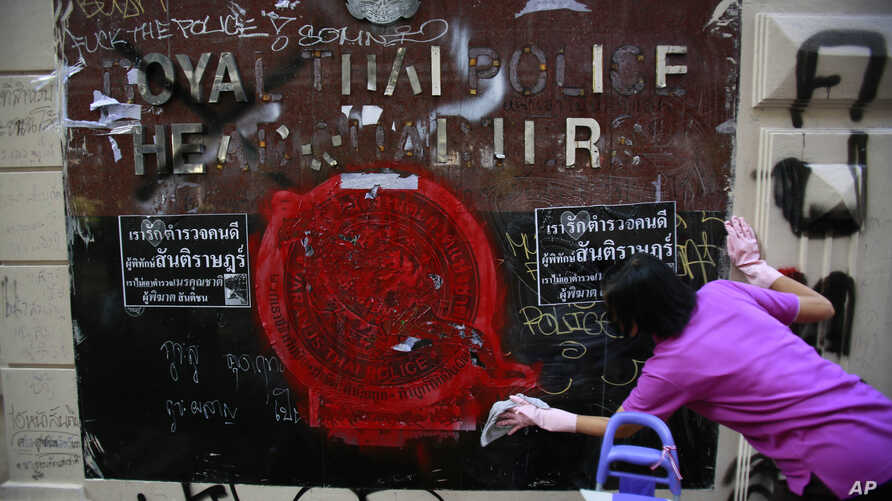 An anti-government protester volunteers to clean graffiti debris from the main gate of the Royal Thai Police Headquarters in Bangkok, Thailand, March 1, 2014.