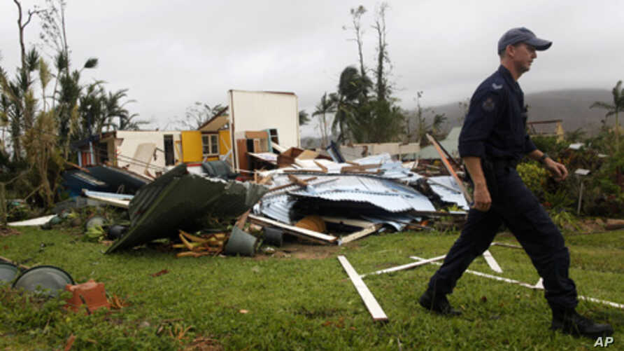 A policeman walks past the remains of a house that was destroyed by Cyclone Yasi in the northern Australian town of Tully, February 3, 2011.