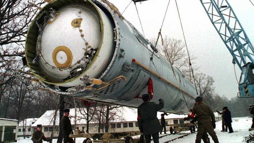 Soldiers prepare to destroy a ballistic SS-19 missile in the yard of the largest former Soviet military rocket base in Vakulenchuk, Ukraine, December 24, 1997.
