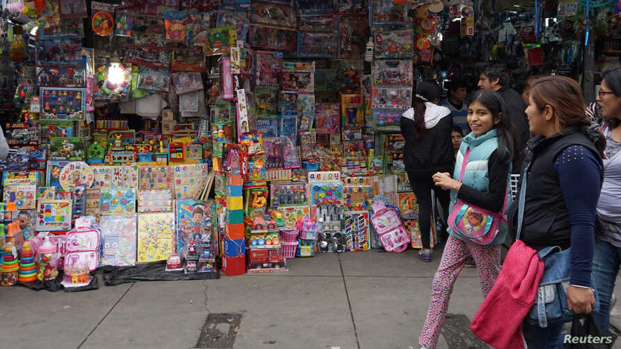 FILE - People walk past a stand that sells toys and other products imported from China at Central Market in Lima, Peru, Aug. 9, 2018.