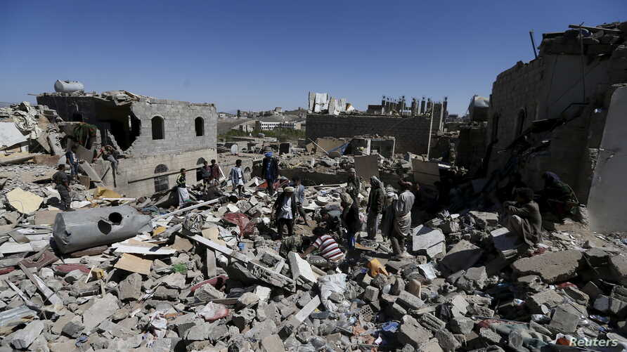 People stand amidst the rubble of houses destroyed by an overnight Saudi-led air strike on a residential area in Yemen's capital Sanaa, May 1, 2015.