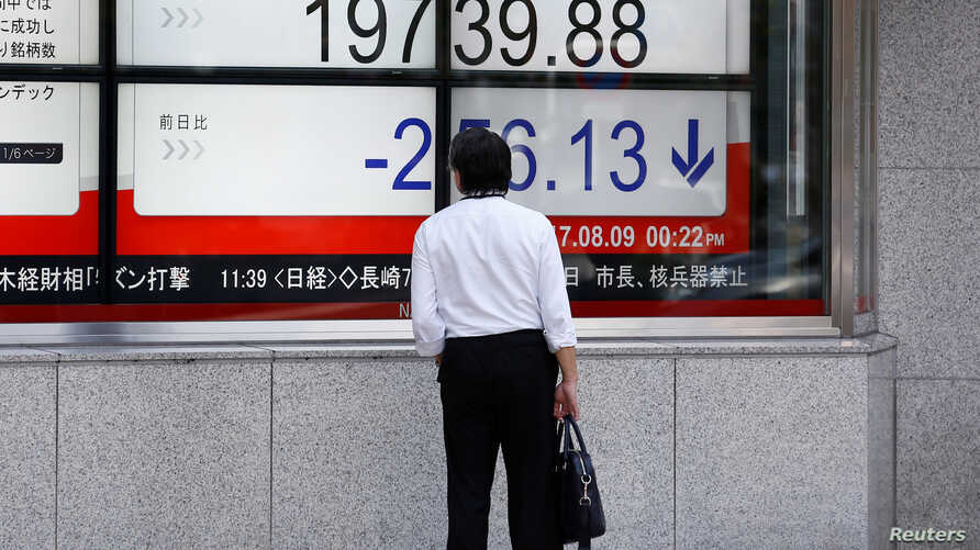 A man looks at an electronic board showing Japan's Nikkei average outside a brokerage at a business district in Tokyo, Aug. 9, 2017.