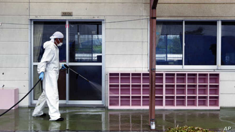 A worker decontaminates radiation from the exterior of Yasawa Kindergarten in Minami-Soma, about 12 miles (20 kilometers) away from the tsunami-crippled Fukushima Dai-ichi nuclear facility, in Fukushima prefecture, northeastern Japan,  August 18, 201