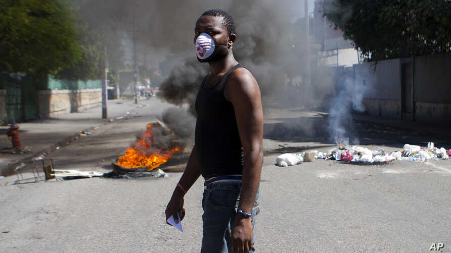A protester walks past burning tires blocking a road as part of a transportation strike in Port-au-Prince, Haiti, Sept. 18, 2017.