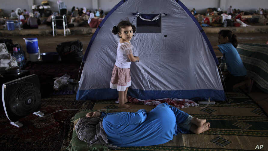 Syrian girl, Raghad Hussein, 3, who fled her home with her family due to fighting between the Syrian army and the rebels, stands by her family's makeshift tent, near Azaz, Syria, Aug. 26, 2012.