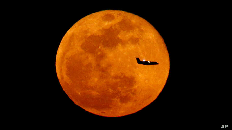 A plane descending into Newark Liberty International Airport crosses over the full moon rising seen from Eagle Rock Reservation, Wednesday, March 23, 2016, in West Orange, N.J.