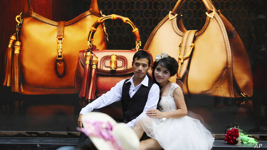 FILE - A couple pose for photos in front of a luxury shop in Hanoi, Vietnam.