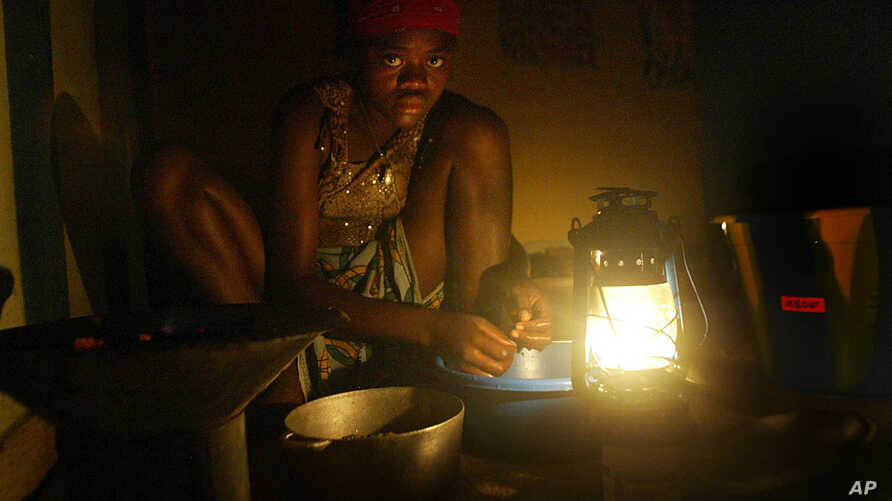 A displaced girl sits in Monrovia hotel without electricity or water preparing lunch for her family on Tuesday, Sept 2, 2003.