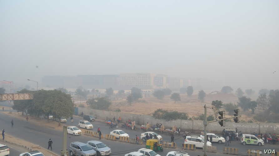 Delhi is blanketed in a grey haze of pollution on Christmas Eve as morning commuters pass by, Dec. 24, 2018.