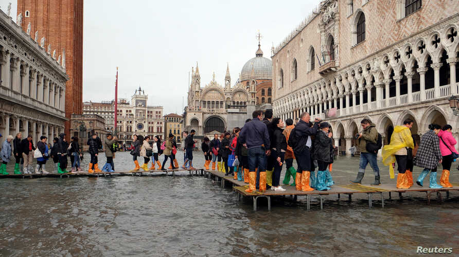 People walk on a catwalk in a flooded Saint Mark Square during a period of seasonal high water in Venice, Italy, Oct. 29, 2018