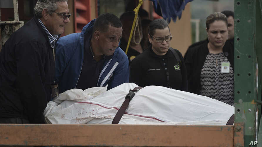 In this Jan. 11, 2018 photo, forensic workers remove the body of a man found fatally shot in San Juan, Puerto Rico. As the Island struggles to recover from Hurricane Maria, it is facing one of the biggest spikes in violent crime in nearly a decade.