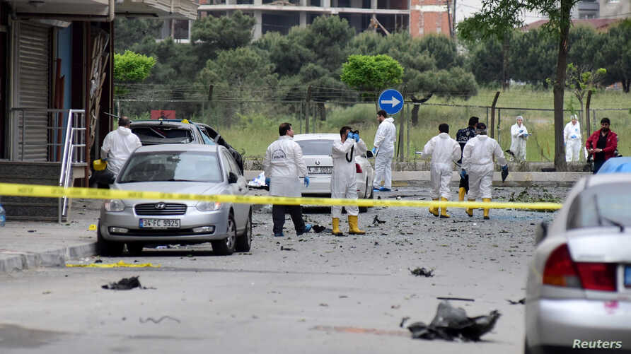 Police forensic experts examine a scene following a vehicle explosion near a military facility in Istanbul, Turkey, May 12, 2016.
