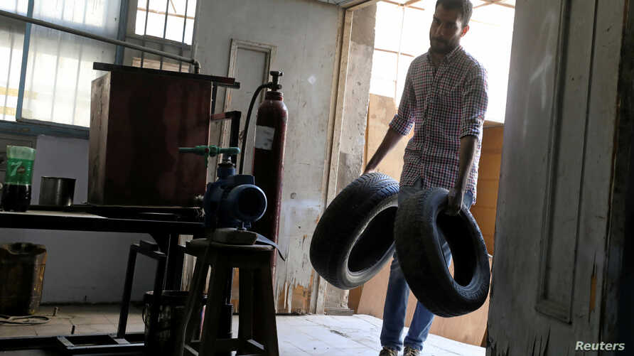 Engineering student Mohamed Amr carries car tires to be used in extracting diesel in Cairo, Egypt, Aug. 23, 2017.