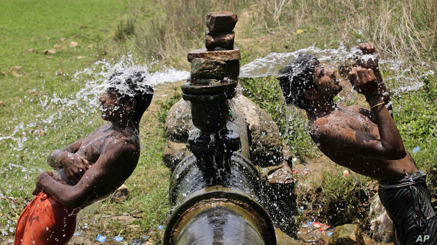 Slum dwellers bathe in water gushing out of a leakage from a pipe on the outskirts of Bhubaneswar, India, May 2, 2013.