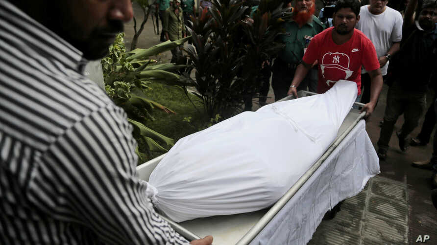 The body of Italian citizen Cesare Tavella, who was gunned down by unidentified assailants, is carried out of a hospital morgue in Dhaka, Bangladesh, Oct. 14, 2015.