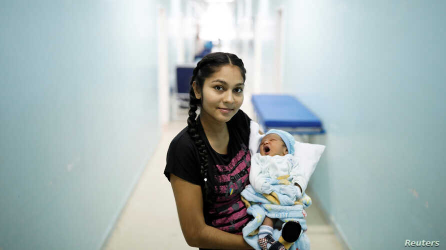 FILE - Jasmilfer, 23, a Venezuelan from Monagas state, holds her five-day-old baby Arjunea at a maternity hospital in Boa Vista, Roraima state, Brazil, Aug. 21, 2018.