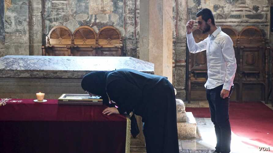 Serbs pray before the tomb of 'holy king' Stefan Dečanski. The church and monastery of Visoki Dečani is protected by soldiers from the NATO-led international peacekeeping force, KFOR. The monastery has been attacked several times since the end ...