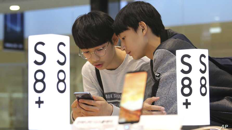 Students try out a Samsung Electronics Galaxy S8 Plus smartphone at its shop in Seoul, South Korea, April 27, 2017.