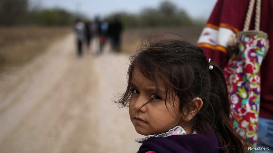 FILE - Alondra Poula, a five-year-old migrant from Nicaragua seeking asylum, walks down a dirt road with her mother after illegally crossing the Rio Grande river into the U.S. from Mexico in Penitas, Texas, Jan. 10, 2019.