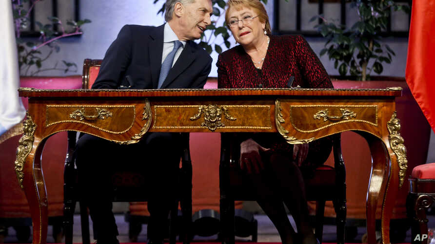 Chile's President Michelle Bachelet and Argentina's President Mauricio Macri chat during in a joint press conference at a La Moneda presidential palace in Santiago, Chile, June. 27, 2017.