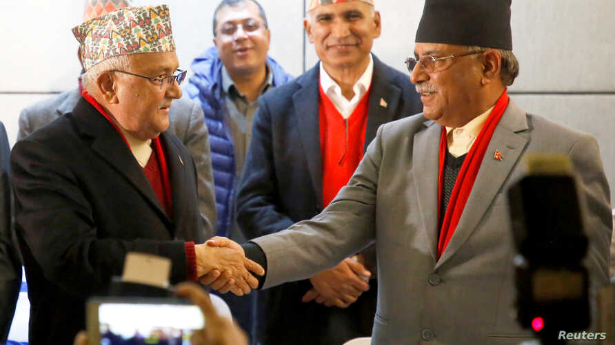 Chairman of Communist Party of Nepal (Unified Marxist-Leninist) (CPN-UML) party Khadga Prasad Sharma Oli, also known as K.P. Oli, (L) shakes hands with the chairman of Communist Party of Nepal (Maoist Centre) Pushpa Kamal Dahal, also known as Prachan
