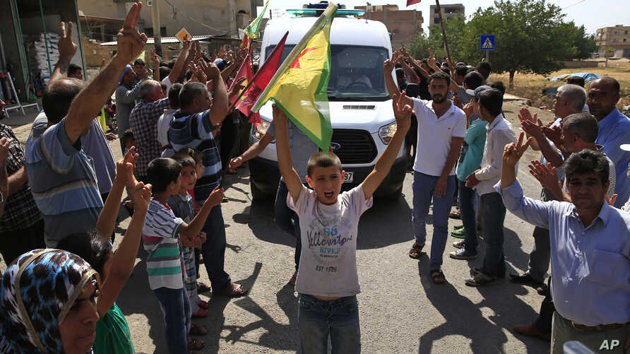 Kurdish supporters line the road as the convoy carrying the body of U.S. citizen Keith Broomfield, killed fighting militants of the Islamic State group in Kobani, passes through Suruc on the Turkey-Syria border, June 11, 2015.