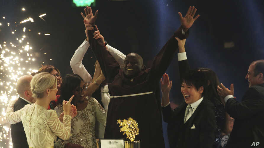 Kenyan teacher Peter Tabichi, center, reacts after winning the $1 million Global Teacher Prize in Dubai, United Arab Emirates, Sunday, March 24, 2019.