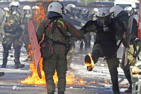Riot police deal with an exploding petrol bomb during riots by anti-austerity demonstrators in Athens' Syntagma [Constitution] square, October 19, 2011.