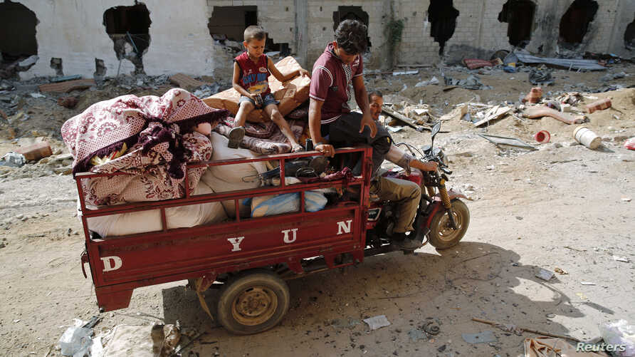 A Palestinian family salvages belongings from the ruins of buildings destroyed by what police said were Israeli airstrikes and shelling in Khuzaa, east of Khan Younis, in the southern Gaza Strip, August 3, 2014.