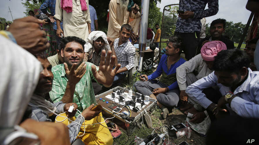 Supporters of the Dera Sacha Sauda sect charge their mobile phones as they squat in a public park near an Indian court in Panchkula, India, Aug. 24, 2017.