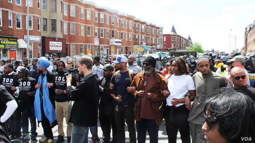 Baltimore police responded briefly with pepper spray before civilians linked arms to form two parallel chains between disquieted demonstrators and the police, Apr 28, 2015 (VOA photo/ Victoria Macchi).