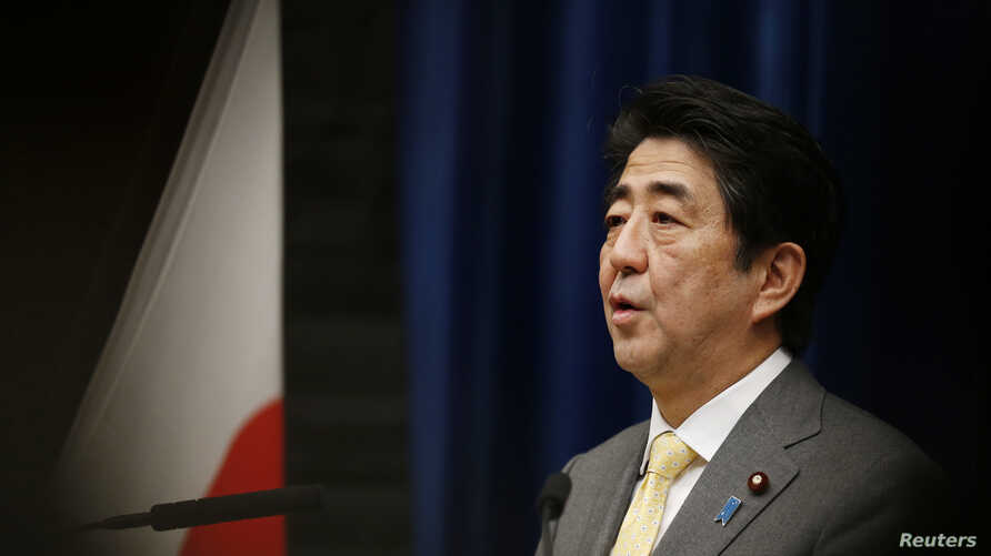 Japan's Prime Minister Shinzo Abe speaks next to the Japanese national flag, attached with a black ribbon to mourn victims a day before the third anniversary of the March 11, 2011 earthquake, tsunami and nuclear crisis that struck the nation's northe
