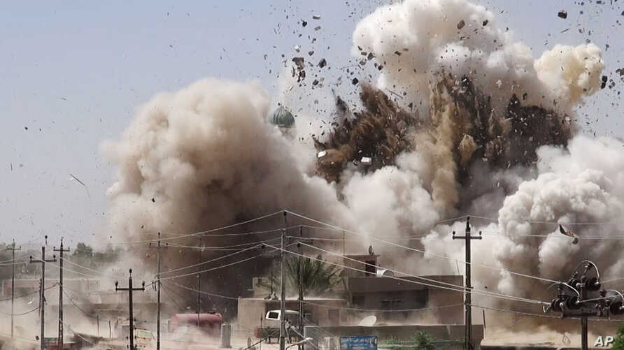 In this undated photo posted on a militant website that frequently carries official statements from the Islamic State extremist group, which has been verified and is consistent with other AP reporting, smoke and debris go up in the air as Shiite's Al