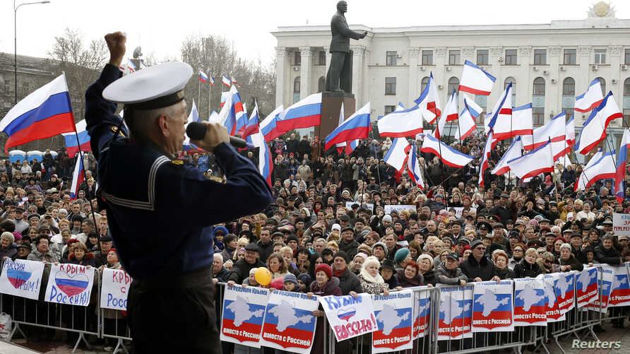 A member of the Russian Song and Dance Ensemble of the Black Sea Fleet performs during a pro-Russian rally in Simferopol, March 9, 2014. Russian forces tightened their grip on Crimea on Sunday despite a U.S. warning to Moscow that annexing the southe...